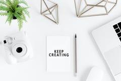Keep que cria citações inspiradores e câmera instantânea no local de trabalho Fotografia de Stock
