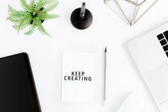 Keep que cria citações inspiradores e portátil no local de trabalho Fotos de Stock Royalty Free