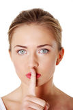 Keep it quiet. Close up portrait of woman making a keep it quiet gesture stock image