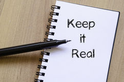 Keep it real write on notebook Stock Photos