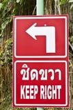 Keep right road sign in Phuket, Thailand. Keep right road sign in the Thai and English languages Stock Image