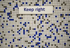 Keep right sign on tiles. Keep right sign on a tiled background in white, blue and gold Stock Image