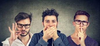 Three secretive men keeping mouth shut. stock image