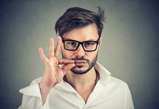 Keep a secret, man zipping his mouth shut. Quiet concept royalty free stock images