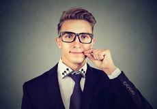 Keep a secret, young man zipping his mouth shut. Quiet concept stock photography