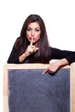 Keep it secret. Woman pointing at blackboard Stock Photo
