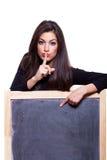 Keep it secret. Woman pointing at blackboard. Keep it secret. Attractive young woman, pointing at a blank blackboard. Studio shot, on white background Stock Photo