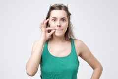 Keep a secret, woman zipping her mouth shut. Quiet concept stock image