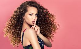 `Keep a secret`, young, beautiful woman is holding finger in front of her lips. stock images