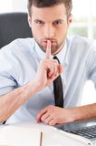 Keep silence!. Confident young man in formalwear holding finger on mouth and looking at camera while sitting at his working place Stock Photos