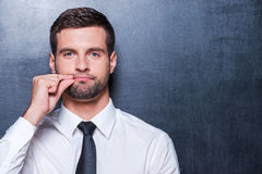 Keep silence!. Handsome young man in formalwear showing a sign of closing mouth and looking at camera while standing against blackboard Stock Photography