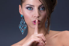 Keep silence signal from Woman wearing shiny blue earring Royalty Free Stock Photography