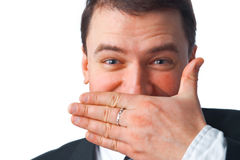 Keep Silent. Close up portrait of young smiling businessman covering mouth with his hand while looking at you over white Royalty Free Stock Photos