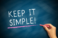 Keep It Simple. Hand with chalk writing Keep It Simple on blackboard stock images