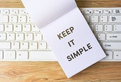 Keep It Simple. On notepad on top of computer keyboard, wooden table background. Retro style effect Royalty Free Stock Photo