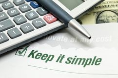 Keep it simple. Printed on book with calculator and pen Royalty Free Stock Photography