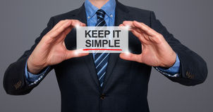 Keep It Simple  on a virtual screen with a businessman holding. It. Grey Stock Image