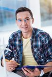 Portrait of handsome man that being at work. Keep smiling. Attractive male expressing positivity while posing on camera, holding folder with papers Royalty Free Stock Photos