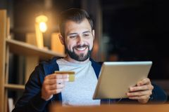 Portrait of positive man that going to buy something. Keep smiling. Attractive male person feeling happiness while looking at his tablet and going to use his Royalty Free Stock Images