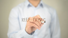 Keep Trying , Man writing on transparent screen Stock Images