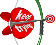 Keep Trying Words Bow Arrow Aiming Bulls-Eye Target. The words Keep Trying on a bow and arrow aiming at a target to illustrate determination, perseverence Stock Images