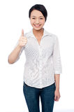 Keep it up! Great work!. Beautiful smiling girl showing thumbs up gesture Stock Photography