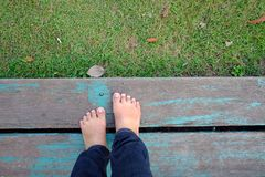 Top view a barefoot female standing on an old wooden bench with green grass below background royalty free stock photography