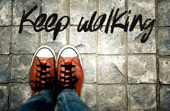 Keep walking word on pavement with shoes background, Inspiration quote Stock Photography