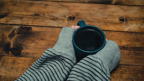 Woman get warming up with a cup of hot coffee. Woman taking a cup of coffee Stock Photos
