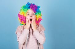 Keep your eyes for a surprise. Cute small girl opened mouth with big surprise. Surprised little girl wearing clown hair royalty free stock photos