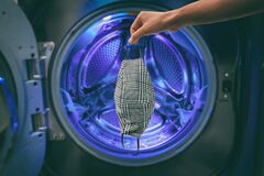 Free Keep Your Reusable Cloth Face Mask Clean By Washing It By Hand Or In Laundry Washing Machine At Home. Cleaning Of Royalty Free Stock Images - 215437589