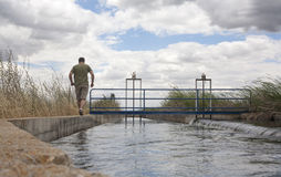 Keeper walking by huge irrigation canal Stock Photo