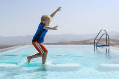 Keeping Balance. Young boy trying to keep his balance whilst jumping from one block to another in an infinity pool Royalty Free Stock Photography