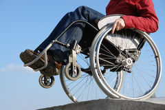 Keeping balance. Closeup of handicapped woman balancing on wheelchair by the concrete kerb over blue sky stock images