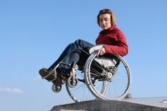 Keeping balance. Wheelchair woman balancing by the concrete kerb over blue sky royalty free stock image