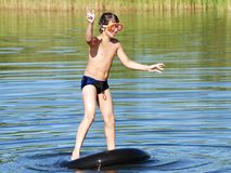 Keeping Balance. The boy keeping balance while standing on a floating tube in a middle of the lake Royalty Free Stock Photos