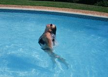 Keeping cool. Caucasian teen in the pool on a hot day enjoying the water Royalty Free Stock Image