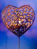 Keeping the flame alive. A tea light in a heart shaped tea light holder Stock Image