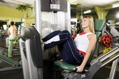 Keeping good shape. Beautiful young blond woman goes in for sport in the gum Stock Photography