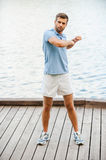 Keeping his body in tonus. Full length of handsome young man exercising while standing on quayside Stock Image
