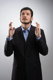 Keeping his fingers crossed. Businessman standing with his finge Stock Photos