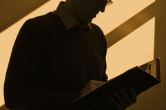 Keeping Late Business Hours. Silhouette of a business person reviewing a file in an office with light and shadow on the wall Stock Photography