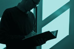 Keeping Late Business Hours. Silhouette of a business person reviewing a file in an office with light and shadow on the wall Royalty Free Stock Photos