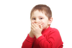 Keeping in laughter. Little boy in red shirt keeping in laughter closing mouth with hands stock photography