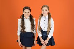 Keeping the look totally trendy. Cute schoolgirls. School children with a fashion forward look. Little girls wearing stock photo