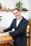 Keeping the minutes. A young brunette office clerk smiling while taking the minutes Royalty Free Stock Images