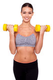 Keeping my body toned. Shot of a beautiful and sporty young woman lifting up weights against white isolated background Stock Photo