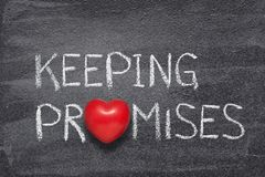 Keeping promises heart. Keeping promises phrase written on chalkboard with red heart symbol royalty free stock image