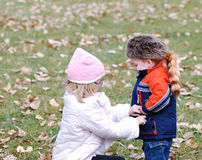 Keeping warm in autumn. Sister adjusting younger brothers coat to keep him warm, autumn scene stock image