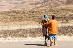 Keeping Warm Together. Two Basotho men walk toward a dry winter field in Leribe District, Lesotho royalty free stock image
